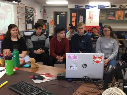 Tenth grade students ask David Gomberg questions via video conference in the classroom.